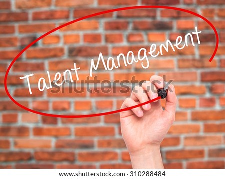 Man Hand writing Talent Management with black marker on visual screen. Isolated on bricks. Business, technology, internet concept. Stock Photo - stock photo