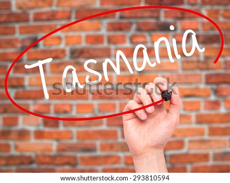 Man Hand writing Tasmania with black marker on visual screen. Isolated on bricks. Business, technology, internet concept. Stock Photo - stock photo