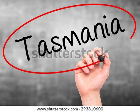 Man Hand writing Tasmania with black marker on visual screen. Isolated on grey. Business, technology, internet concept. Stock Photo - stock photo