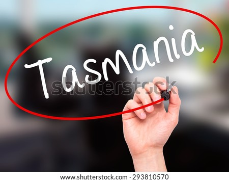 Man Hand writing Tasmania with black marker on visual screen. Isolated on office. Business, technology, internet concept. Stock Photo - stock photo
