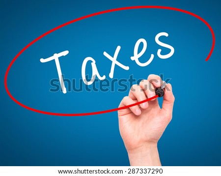 Man Hand writing Taxes with marker on transparent wipe board. Isolated on blue. Business, internet, technology concept. Stock Photo - stock photo
