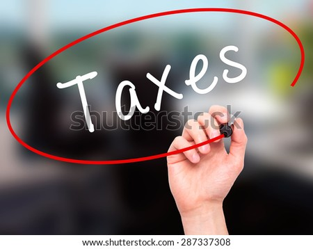 Man Hand writing Taxes with marker on transparent wipe board. Isolated on office. Business, internet, technology concept. Stock Photo - stock photo