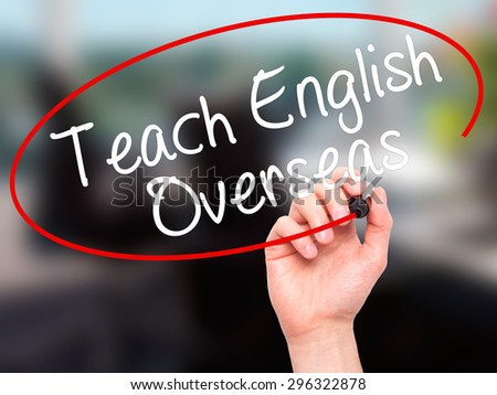 Man Hand writing Teach English Overseas with black marker on visual screen. Isolated on office. Business, technology, internet concept. Stock Photo - stock photo