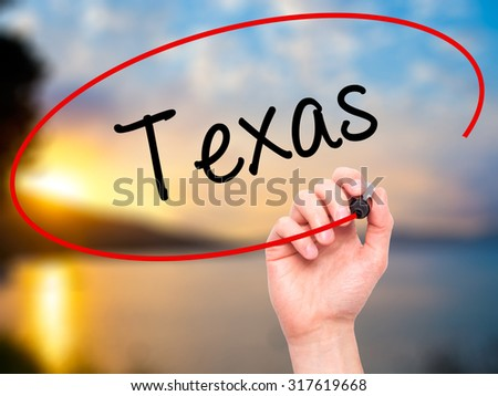 Man Hand writing Texas  with black marker on visual screen. Isolated on nature. Business, technology, internet concept. - stock photo