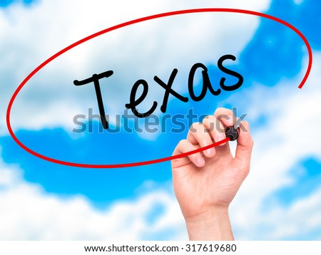 Man Hand writing Texas  with black marker on visual screen. Isolated on sky. Business, technology, internet concept. - stock photo