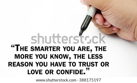 "Man Hand writing ""the smarter you are,the more you know,the less reason you have to trust or love or confide"" with black marker on visual screen. Isolated white background."