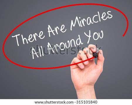 Man Hand writing There Are Miracles All Around You  with black marker on visual screen. Isolated on grey. Business, technology, internet concept. Stock Photo - stock photo