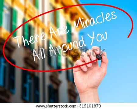Man Hand writing There Are Miracles All Around You  with black marker on visual screen. Isolated on city. Business, technology, internet concept. Stock Photo - stock photo