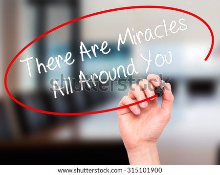 Man Hand writing There Are Miracles All Around You  with black marker on visual screen. Isolated on office. Business, technology, internet concept. Stock Photo - stock photo