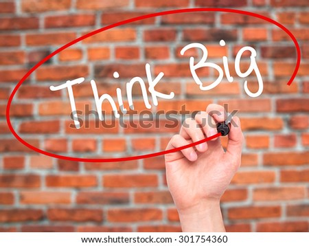 Man Hand writing Think Big with black marker on visual screen. Isolated on bricks. Business, technology, internet concept. Stock Photo - stock photo
