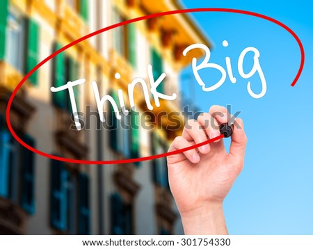 Man Hand writing Think Big with black marker on visual screen. Isolated on city. Business, technology, internet concept. Stock Photo - stock photo