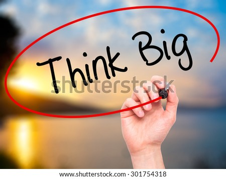 Man Hand writing Think Big with black marker on visual screen. Isolated on nature. Business, technology, internet concept. Stock Photo - stock photo