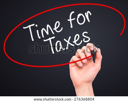 Man Hand writing Time for Taxes with marker on transparent wipe board. Isolated on black. Business, internet, technology concept.  Stock Photo - stock photo