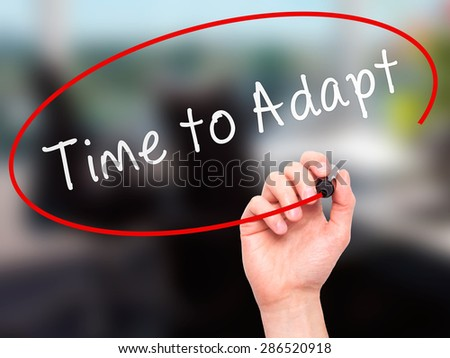 Man hand writing Time to Adapt on visual screen. Business,help, internet, technology concept. Isolated on office. Stock Photo - stock photo