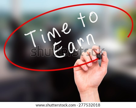 Man Hand writing Time to Earn with marker on transparent wipe board. Isolated on office. Business, internet, technology concept.  Stock Photo - stock photo