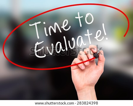 Man Hand writing Time to Evaluate with marker on transparent wipe board. Isolated on office. Business, internet, technology concept. Stock Photo - stock photo