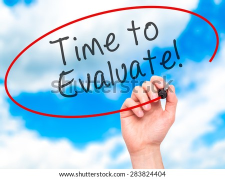 Man Hand writing Time to Evaluate with marker on transparent wipe board. Isolated on sky. Business, internet, technology concept. Stock Photo - stock photo