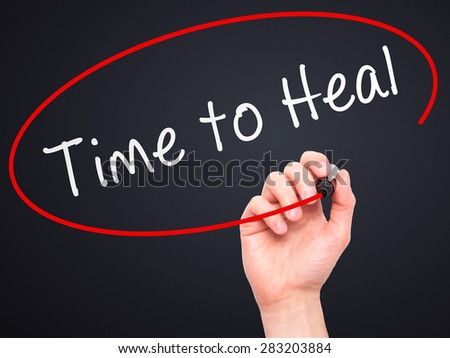 Man Hand writing Time to Heal with marker on transparent wipe board. Isolated on black. Business, internet, technology concept. Stock Photo - stock photo