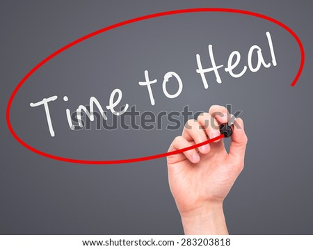 Man Hand writing Time to Heal with marker on transparent wipe board. Isolated on grey. Business, internet, technology concept. Stock Photo - stock photo