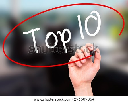 Man Hand writing Top 10 with black marker on visual screen. Isolated on office. Business, technology, internet concept. Stock Photo - stock photo