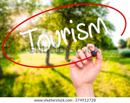 Man Hand writing Tourism  with black marker on visual screen. Isolated on background. Business, technology, internet concept. Stock Photo - stock photo
