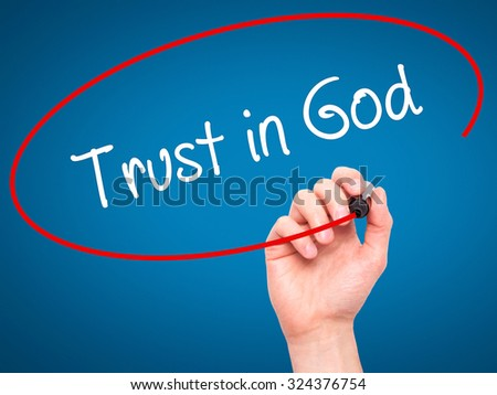 Man Hand writing Trust in God with black marker on visual screen. Isolated on blue. Business, technology, internet concept. Stock Photo - stock photo