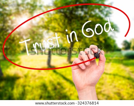 Man Hand writing Trust in God with black marker on visual screen. Isolated on nature. Business, technology, internet concept. Stock Photo - stock photo