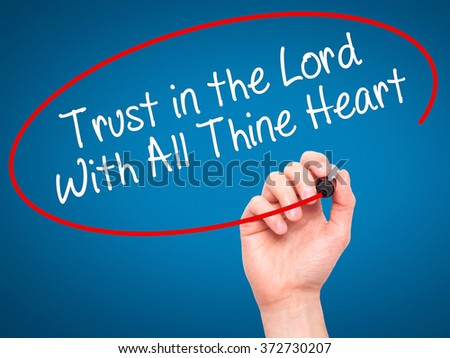 Man Hand writing Trust in the Lord With All Thine Heart with black marker on visual screen. Isolated on background. Business, technology, internet concept. Stock Photo