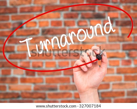 Man Hand writing Turnaround with black marker on visual screen. Isolated on bricks. Business, technology, internet concept. Stock Photo - stock photo