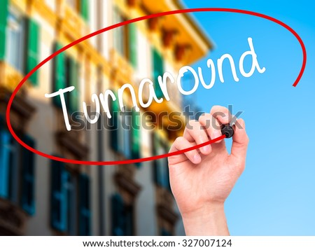 Man Hand writing Turnaround with black marker on visual screen. Isolated on city. Business, technology, internet concept. Stock Photo - stock photo
