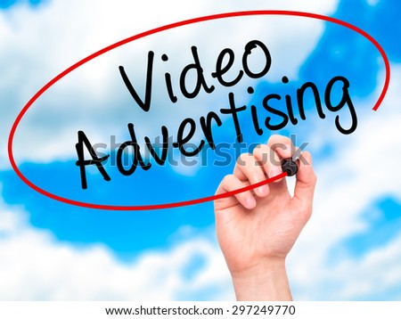 Man Hand writing Video Advertising with black marker on visual screen. Isolated on sky. Business, technology, internet concept. Stock Photo - stock photo