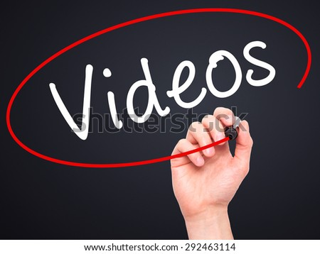 Man Hand writing Videos with black marker on visual screen. Isolated on black. Business, technology, internet concept. Stock Image - stock photo