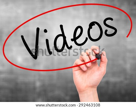 Man Hand writing Videos with black marker on visual screen. Isolated on grey. Business, technology, internet concept. Stock Image - stock photo