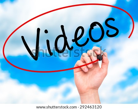 Man Hand writing Videos with black marker on visual screen. Isolated on sky. Business, technology, internet concept. Stock Image - stock photo