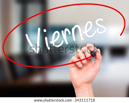 Man Hand writing Viernes (Friday in Spanish) with black marker on visual screen. Isolated on office. Business, technology, internet concept. Stock Photo - stock photo