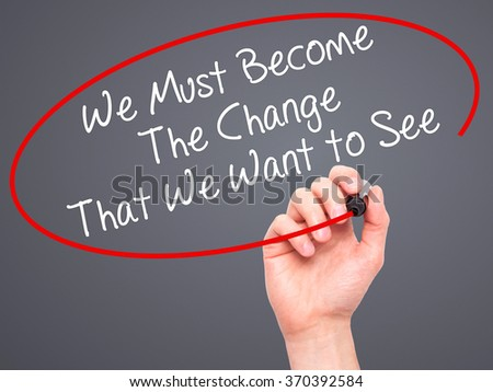 Man Hand writing We Must Become The Change That We Want to See with black marker on visual screen. Isolated on background. Business, technology, internet concept. Stock Photo