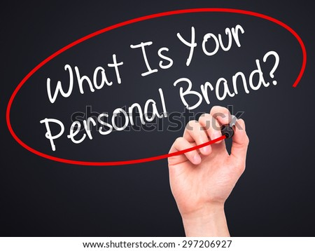 Man Hand writing What Is Your Personal Brand? with black marker on visual screen. Isolated on black. Business, technology, internet concept. Stock Photo