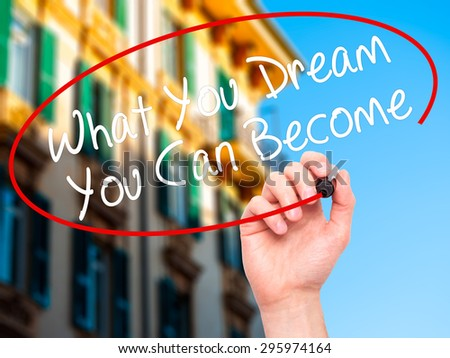 Man Hand writing What You Dream You Can Become with black marker on visual screen. Isolated on city. Business, technology, internet concept. Stock Photo - stock photo