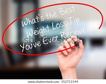 Man Hand writing Whats the Best Weight Loss Tip You've Ever Received? with black marker on visual screen. Isolated on background. Business, technology, internet concept. Stock Photo
