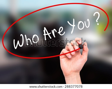 Man Hand writing Who Are You with black marker on visual screen. Isolated on office. Business, technology, internet concept. Stock Image - stock photo
