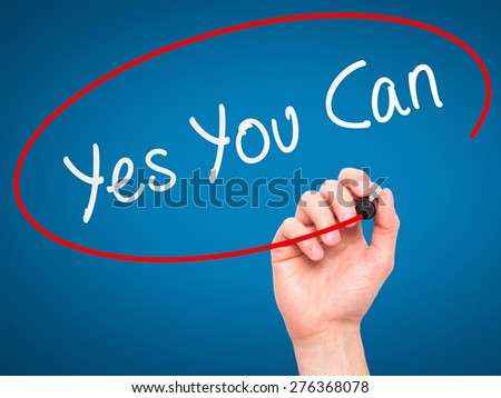 Man Hand writing Yes You Can with marker on transparent wipe board. Isolated on blue. Business, internet, technology concept.  Stock Photo - stock photo