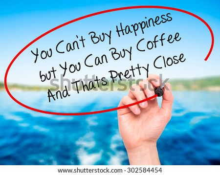 Man Hand writing You Cant Buy Happiness but You Can Buy Coffee And Thats Pretty Close with black marker on visual screen. Isolated on nature. Business, technology, internet concept.