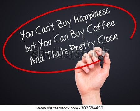 Man Hand writing You Cant Buy Happiness but You Can Buy Coffee And Thats Pretty Close with black marker on visual screen. Isolated on black. Business, technology, internet concept.