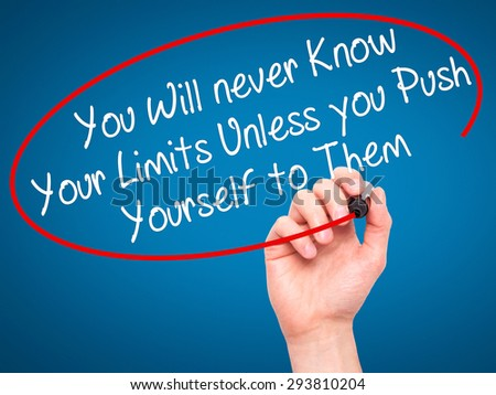 Man Hand writing You Will never Know Your Limits Unless you Push Yourself to Them with black marker on visual screen. Isolated on blue. Business, technology, internet concept. Stock Photo