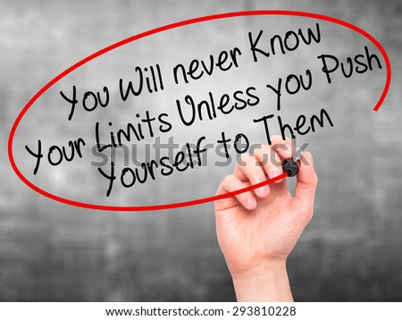 Man Hand writing You Will never Know Your Limits Unless you Push Yourself to Them with black marker on visual screen. Isolated on grey. Business, technology, internet concept. Stock Photo