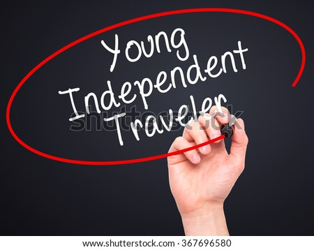 Man Hand writing Young Independent Traveler with black marker on visual screen. Isolated on background. Business, technology, internet concept. Stock Photo