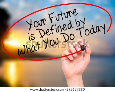 Man Hand writing Your Future is Defined by What You Do Today with black marker on visual screen. Isolated on nature. Business, technology, internet concept. Stock Image - stock photo