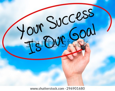 Man Hand writing Your Success Is Our Goal with black marker on visual screen. Isolated on sky. Business, technology, internet concept. Stock Photo