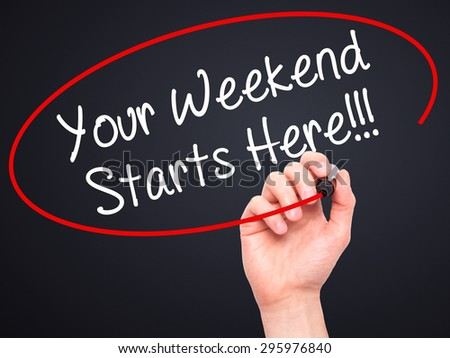 Man Hand writing Your Weekend Starts Here!!! with black marker on visual screen. Isolated on black. Business, technology, internet concept. Stock Photo