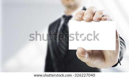 man handing a blank business card over white background - stock photo